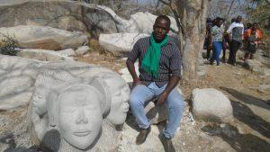 L'artiste sculpteur burkinabè posant fièrement à côté de son œuvre